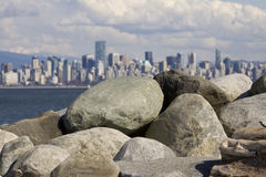 Spanish Banks, with Vancouver skyline behind. Rock pile at Spanish Banks, with Vancouver skyline behind royalty free stock images