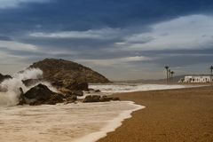 A Spanish beach with crashing waves and palm trees royalty free stock photography