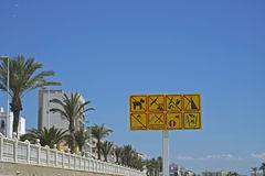 Spanish beach warning signs. Against sky and buildings Royalty Free Stock Photo
