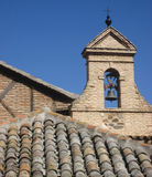 Spanish Bell Tower. A Spanish bell tower sits atop an old tiled roof in Toledo, Spain royalty free stock photos