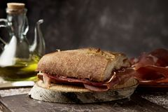 Spanish bocadillo de jamon, serrano ham sandwich. Closeup of a typical spanish bocadillo de jamon, a serrano ham sandwich, on a rustic wooden table, next to a Royalty Free Stock Images