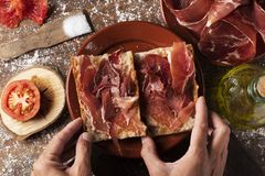 Spanish bocadillo de jamon, serrano ham sandwich. High angle view of a man preparing a typical spanish bocadillo de jamon, a serrano ham sandwich, on a rustic Royalty Free Stock Photos