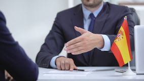 Spanish boss signing employment contract with immigrant employee, shaking hand. Stock footage stock video footage
