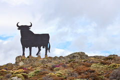Spanish Bull. Osborne black Spanish bull, symbol of Spain. Landscape with cloudy sky Stock Photos