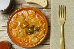 Spanish callos. Bread, wine, paprika, napkin and golden fork on a wooden table Stock Image