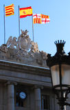 Spanish and Catalan flags. A view of the Spanish and Catalan flags flying on a public building in Barcelona with a street lamp in the foreground Stock Images