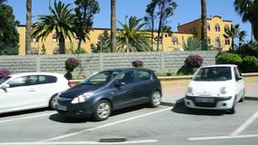 Spanish Ceuta enclave city life scenes. Ceuta, Spain - Circa 2019: Spanish Ceuta enclave city life scenes, parked cars and Iberian occre building as seen from a stock footage