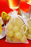 Spanish champagne and the twelve grapes of luck. Some glasses with spanish champagne and sachets with the twelve grapes of luck, traditional on the New Year in Stock Images