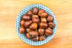 Spanish Chestnuts in a vintage dish on wooden plate background Royalty Free Stock Photos