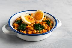 Spanish chickpea and spinach stew with eggs on light gray background. Spanish cuisine royalty free stock image