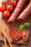 Spanish chorizo sausage with basil on chopping board Stock Photo