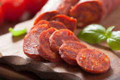 Spanish chorizo sausage with basil on chopping board Royalty Free Stock Photography