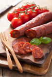 Spanish chorizo sausage with basil on chopping board Royalty Free Stock Images