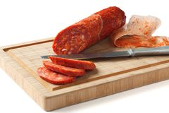 Spanish chorizo sausage with knife on wooden board Stock Photo