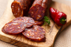 Spanish chorizo sausage with parsley on rustic boa Royalty Free Stock Photos