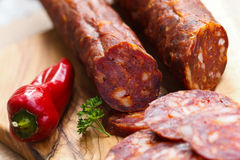 Spanish chorizo sausage with parsley on rustic boa Stock Photos