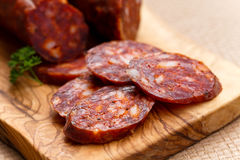 Spanish chorizo sausage with parsley on rustic boa Royalty Free Stock Photo