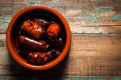 Spanish Chorizo Sausage. Chorizo sausage tapas dish cooked in an earthenware bowl and served on a rustic wooden table Stock Images