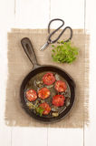 Spanish chorizo with tomato and onion in a cast iron pan Stock Photos