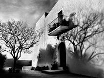 Spanish Church. Black and white exterior of stone Spanish church with balcony and shadow of bare branched tree Stock Photography