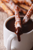 Spanish churros dipped in a hot chocolate macro. vertical Stock Photo