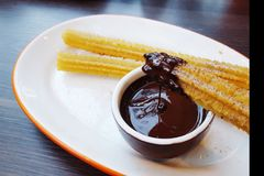 Spanish churros dipping in chocolate sauce Royalty Free Stock Photography
