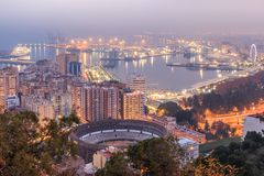 Malaga by night with harbor and bulls arena stock photography
