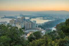 Cityscape Malaga by sunset with bulls arena and harbor stock image