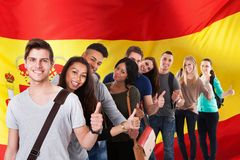 Spanish classes. Group Of Happy Multi Ethnic Students Standing In Front Of Spain Flag Showing Thumb Up Royalty Free Stock Photos