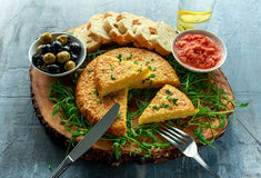 Spanish classic tortilla with potatoes, olives, tomatoes, rucola, bread and herbs. Stock Image
