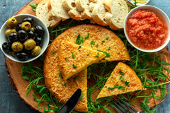 Spanish classic tortilla with potatoes, olives, tomatoes, rucola, bread and herbs. Stock Images