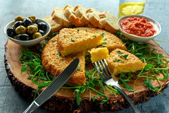 Spanish classic tortilla with potatoes, olives, tomatoes, rucola, bread and herbs. Royalty Free Stock Photos
