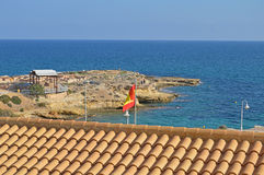 Spanish Clay Roof And A Roman Settlement. Looking over the roof of a Spanish building to the Roman settlement of El Campello Royalty Free Stock Images