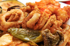 Spanish combo platter. Closeup of a spanish combo platter with fries, grilled pepper and fried shrimps and calamares royalty free stock image