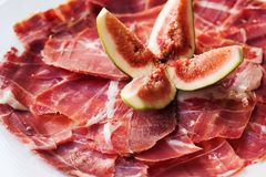 Spanish Cuisine tapas food Jamon with fig. Beautiful appetite slices of raw pork meat, white plate background. Spanish Cuisine tapas food Jamon with fig Stock Image