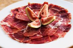 Spanish Cuisine tapas food Jamon with fig. Beautiful appetite slices of raw pork meat, white plate background. Spanish Cuisine tapas food Jamon with fig Royalty Free Stock Image