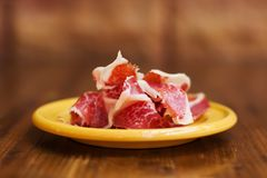 Spanish cuisine tapas food Jamon in a yellow plate. Beautiful appetite slices of raw pork meat. Close-up photo, soft. Focus, brown blurred abstract background Royalty Free Stock Photo
