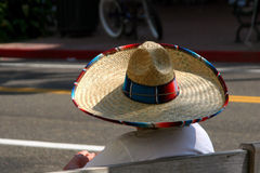 Spanish Days Sombrero. During an Old Spanish Days celebration in downtown Santa Barbara, California, a woman sits on a bench wearing a sombrero stock image