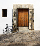 Spanish Door and Cobbled Street. Bike tied against doorway in Spanish white villages - vejer royalty free stock photo