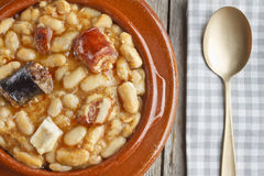 Spanish fabada in an earthenware dish with a golden spoon Royalty Free Stock Photo