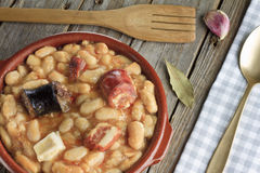 Spanish fabada in an earthenware dish with a wooden fork Stock Photos