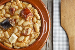 Spanish fabada in an earthenware dish and a wooden spoon Royalty Free Stock Images