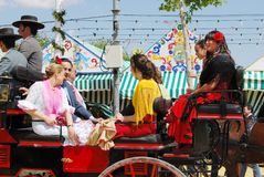 Spanish family in horse drawn carriage. Spanish family in traditional dress travelling in a horse drawn carriage at the Seville Fair, Seville, Seville Province Stock Photo