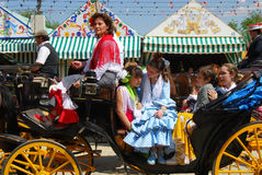 Spanish family in horse drawn carriage. Spanish family in traditional dress travelling in a horse drawn carriage at the Seville Fair, Seville, Seville Province Stock Photography