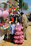 Spanish family at a snack and toy stall. Spanish family in traditional dress standing alongside a snack stall at the Seville Fair, Seville, Seville Province Royalty Free Stock Photography