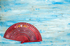 Spanish fan on blue wooden background Royalty Free Stock Photos