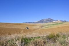 Spanish farmland with a tractor working in the fields of Andalucia. Mountainous spanish farmland with a tractor plowing undulating arable fields under a clear Stock Image