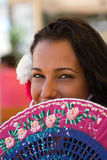 Spanish Female with Fan at Feria. Spanish girl hides smile behind hand painted fan at local feria in south of spain stock photo