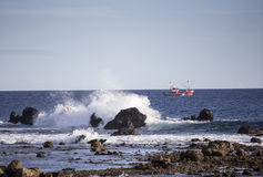 Spanish fishing boat. Tenerife fishing boat taken near the harbour at Las Galletas with waves breaking on rocks in the foreground stock photo
