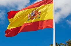 Spanish flag against the blue sky. Sunny weather. It`s windy. White clouds against blue sky Royalty Free Stock Photography